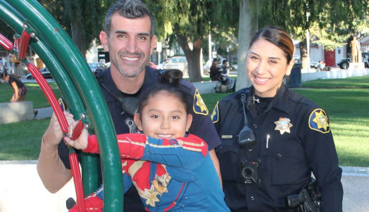 Two police officers with a child at the park