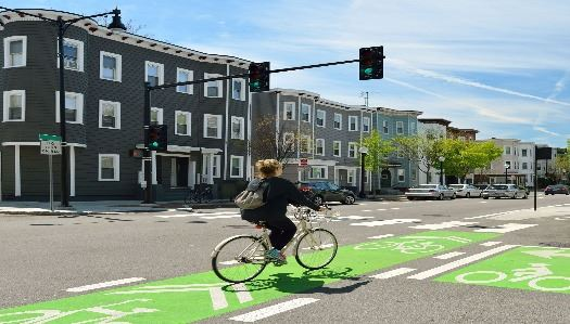 woman riding green bike lane Opens in new window